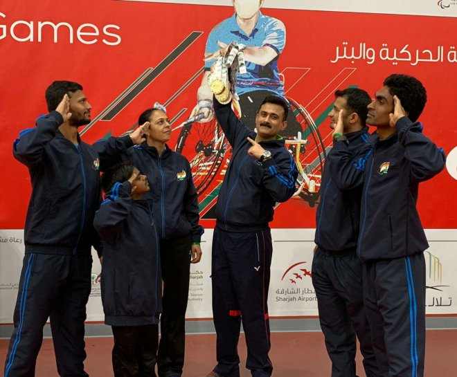 Image of Khanna holding disabled players' medals while the players salute on scene at an event in Sharjah. Players are dressed in navy blue attire and posing in front of a bright red poster of the Sharjah event