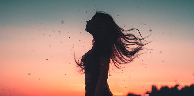 silhouette of woman over sunet sky background with hair flying