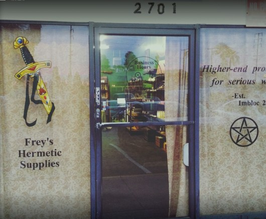 Photo of the front door of Frey's Hermetic Supplies, with curtained windows on each side of the door, a sword on one window, and a pentacle on the other.