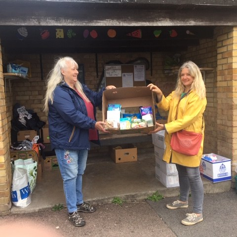 Jaqui Smith (Left) Chair of the Paganhill Community Group) receives the first of many food donations from Amanda-Jane Strover of the Stroud District Foodbank for the Paganhill Bus Stop Shop