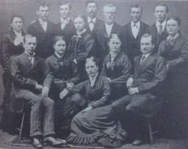 St. John's Choir. Sitting: H.A. Boe, Miss S. Haugen (Mrs. A.T. Brandvold), Miss Esther Thompson, Miss Marie Aaker, Bersven Johnson. Standing: Miss Broin, Nils P. Langem (?), S.A. Siverts, Miss Birgitte Muus, Torsten Kvamme, Torkelson, Nuppen, Ole Kolseth, Miss Bakkethun.