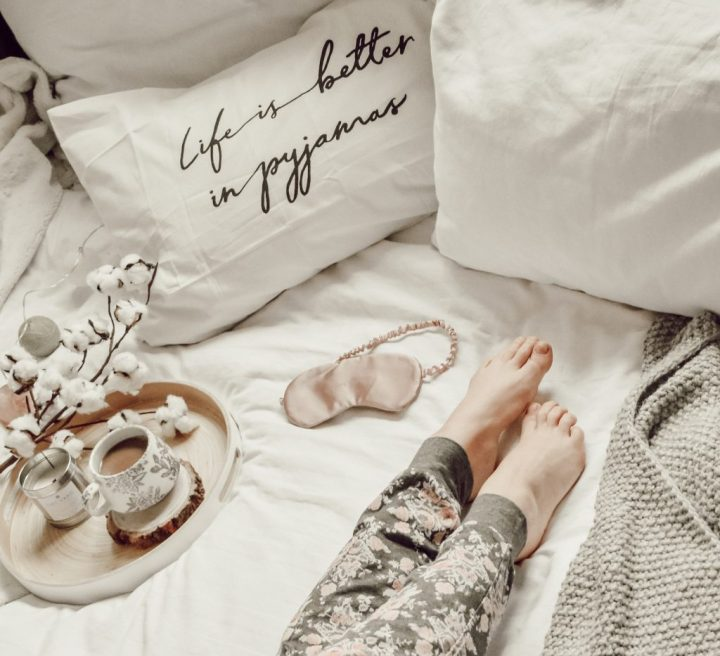 Flatlay photograph image above the bed showing a birds eye view of the bed surface and featuring a tray with coffee cup and candle, printed pillowcases, blankets and duvet, and lady wearing pyjama bottoms