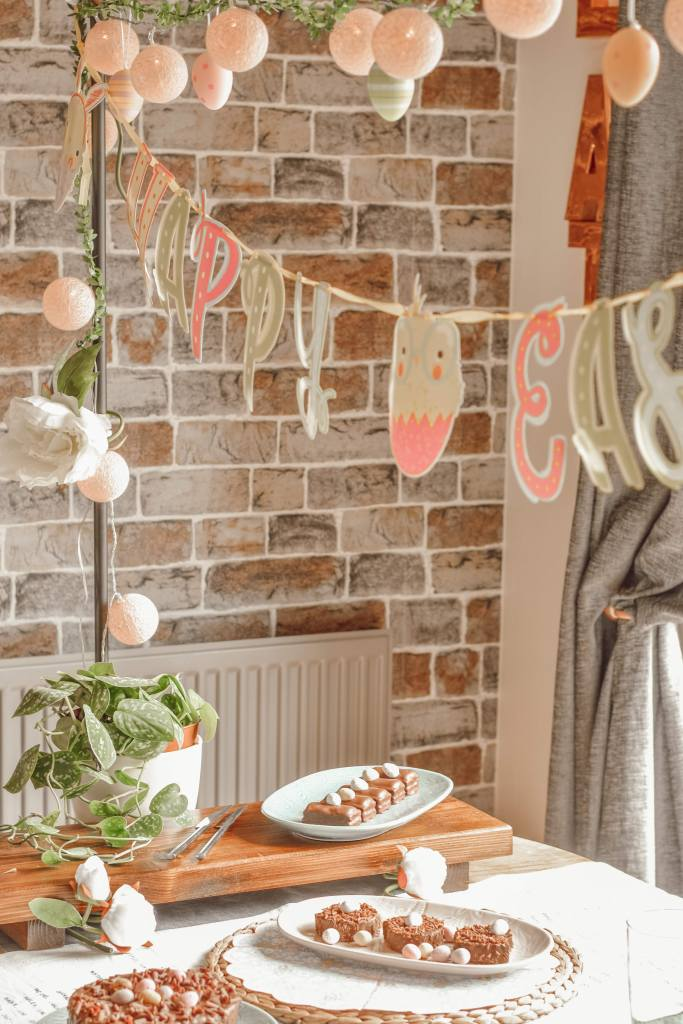 easter bunting hung over a dinging table dressed with chocolate easter food and plants