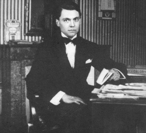 Portrait de Jean Moulin, dans un salon, assis, un livre � la main.