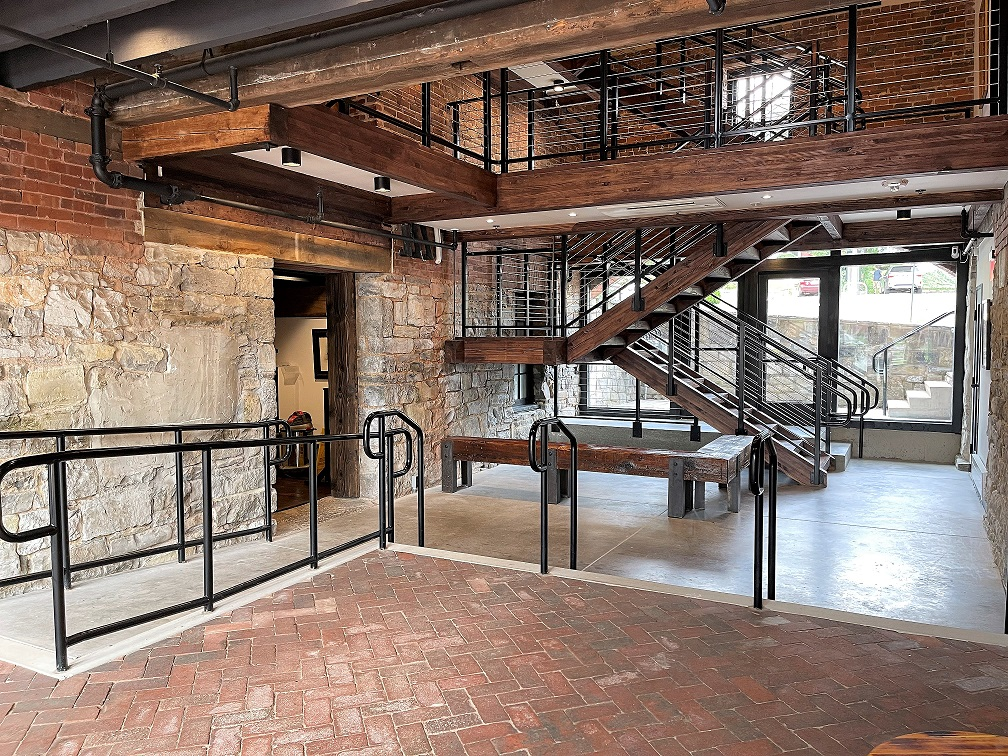 Mill foyer with brick floor and walls, stone walls, and open staircase.