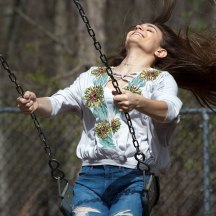 Teen girl swinging on swings
