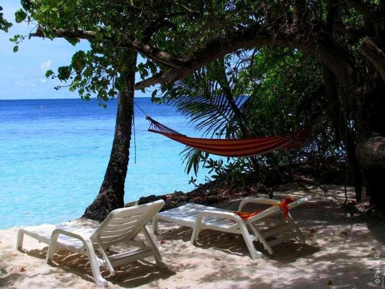 Тенистый пляж с гамаком и видом на бирюзовое море