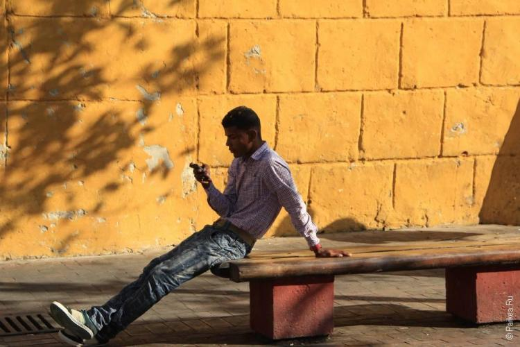 Мужчина на лавке с телефоном