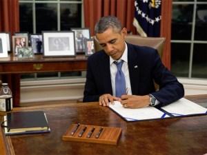 O presidente dos EUA, Barack Obama, assina legislação garantindo pagamento aos membros das Forças Armadas (Foto: Pete Souza/White House)