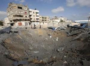 Palestinos observam uma cratera que foi causada por um ataque aéreo israelense na cidade de Gaza, nesta quinta-feira, 3 de julho