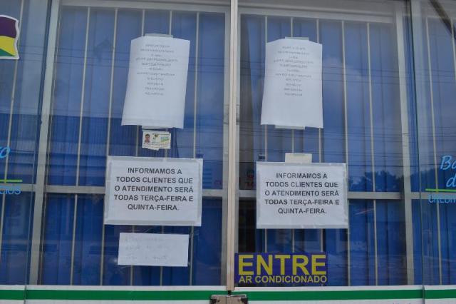 Cartazes anunciam horários de atendimento no banco que funciona apenas dois dias na semana