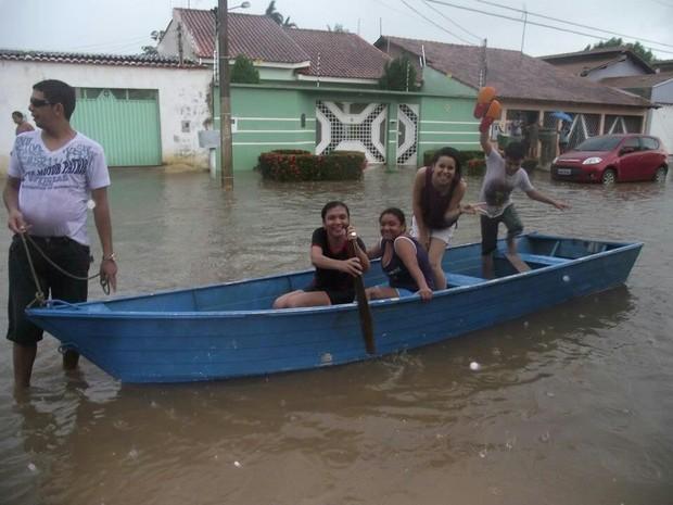 Moradores em barco no meio da rua após forte chuva em Porto Velho (Foto: Paulo Sergio/Arquivo Pessoal)