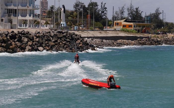 Triatleta some no mar durante competição do Ironman, em Fortaleza