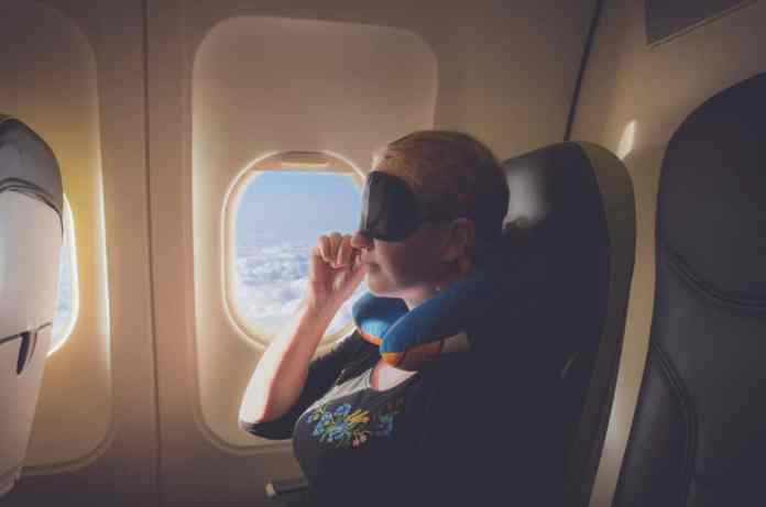 Summer Travel with Chronic Pain woman on plane with support pillow