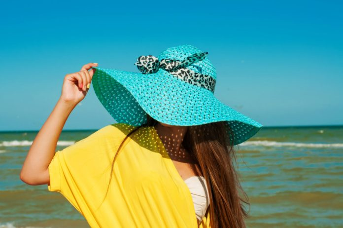 protect your skin from sunburn woman wearing wide brimmed hat on beach
