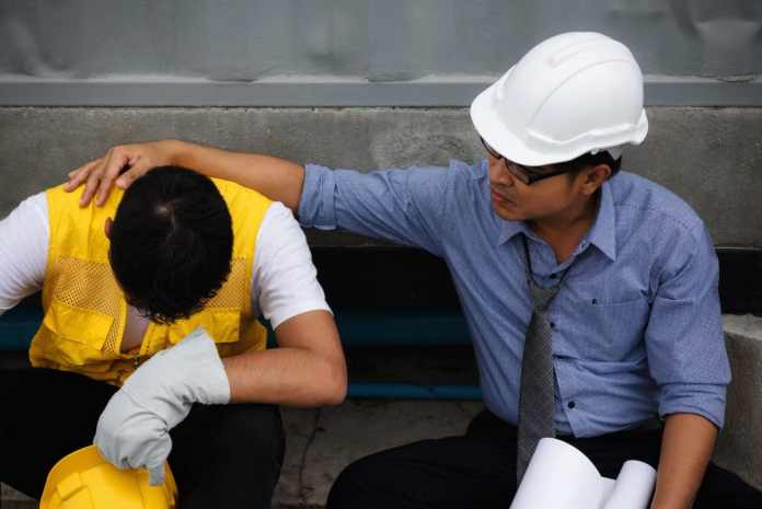 How Chronic Pain Can Affect Job Performance construction employee in pain talking to foreman