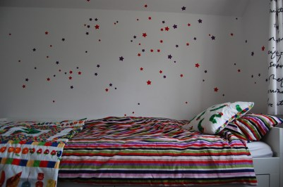 Toddler's bedroom with star vinyl wall stickers and stripey bed linen