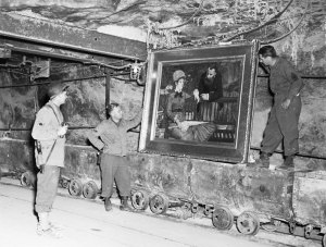 """In this April 25, 1945 image released by the U.S. National Archives, U.S. Army personnel stand by a painting called, """"Wintergarden,"""" by French Impressionist Edouard Manet, which was discovered in the vault in Merkers, Germany. Holocaust survivors and their relatives, as well as art collectors and museums, can go online beginning Monday, Oct. 18, 2010 to search a historical database of more than 20,000 art objects stolen in German-occupied France and Belgium from 1940 to 1944. (AP Photo/U.S. National Archives)"""
