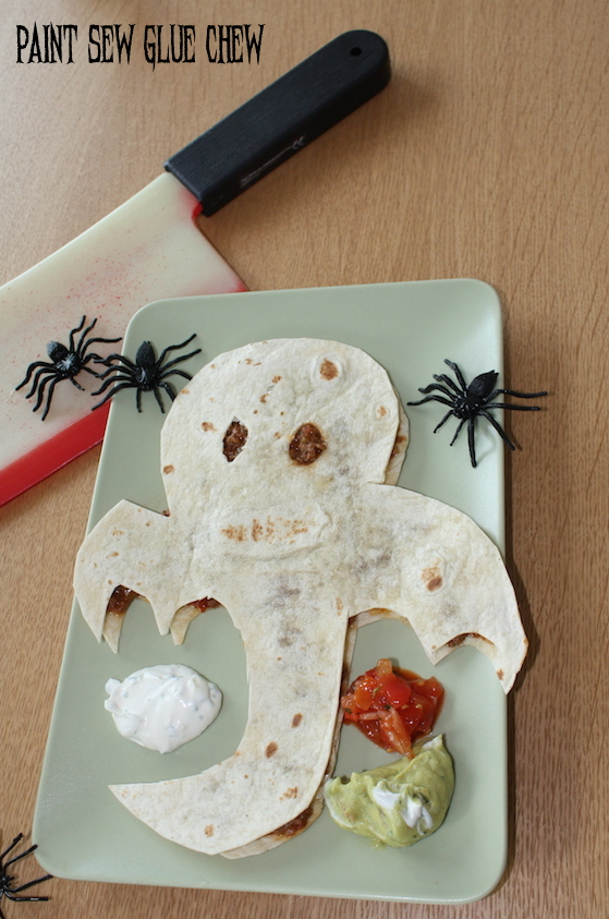 Ghostly quesadilla on a plate with spiders and machette