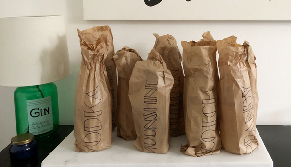Liquor bottles in brown bags and gin light fitting for speakeasy party