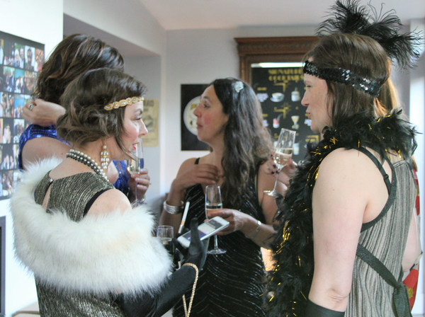 Flappers in 1920s dresses at speakeasy party.