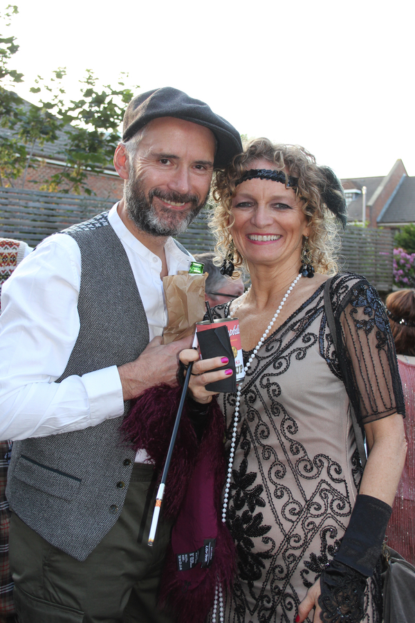 Party guests in 1920s outfits at speakeasy party