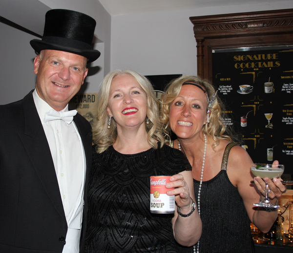 Flappers and 1920s gent in top hat and tails at prohibition party