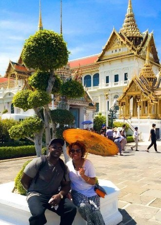 couple in Thailand sitting with umbrella