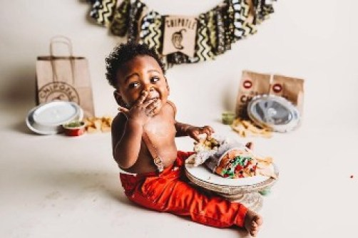 Toddler boy eating some of his burrito cake.