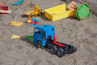 Toy trucks in the sand at the beach