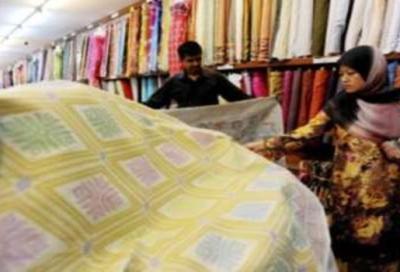 Seorang pembantu kedai menunjukkan pelbagai jenis kain dan sampin dari jenis biasa hingga yang bermutu tinggi untuk dibuat baju melayu kepada pelanggan.
