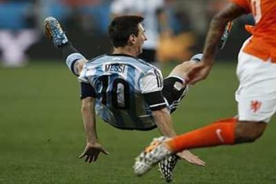 PENYERANG Argentina, Lionel Messi terjatuh selepas pergerakannya dikawal ketat pertahanan Belanda pada aksi perlawanan separuh akhir Piala Dunia