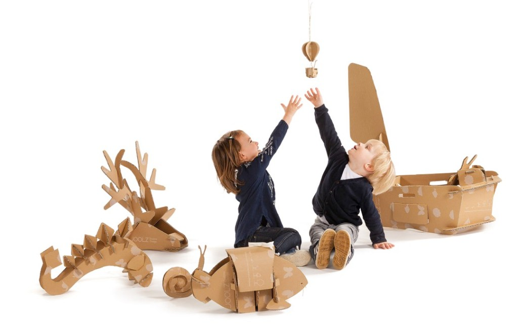 Happy children playing with transformable cardboard packaging.