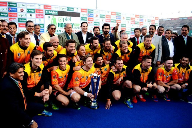 World XI field hockey captain Roderick Weusthof (C) holds the trophy with teamates after winning the series against Pakistan at the National Hockey Stadium in Lahore on January 21 2018. World XI won the two