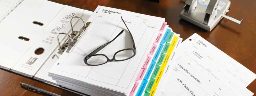 A Glasses is placed bundle of papers on desk