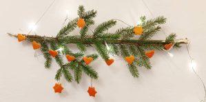 Mandarinhéj díszek fenyőágon fényfüzérrel