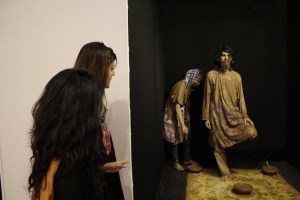 """Two female visitors look on as performance artists present their exhibit 'Rang-e-Khaak' at """"We Are All Mad Here"""" exhibition"""