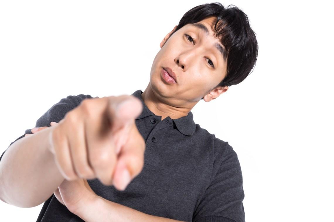 「憮然とした態度で指摘する男性」の写真[モデル:大川竜弥]