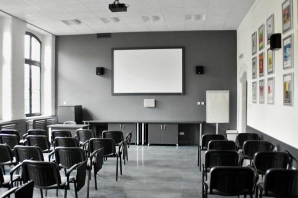wnętrze sali multimedialnej, ekran nascianie ikrzesła