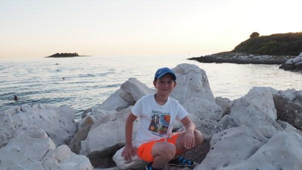 Chłopiec siedzący naskałach. Zanim morze...