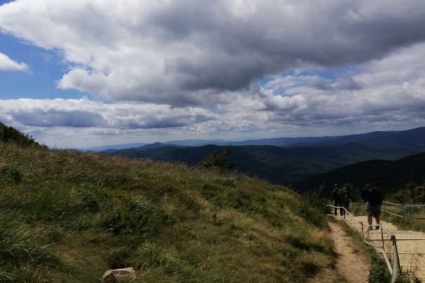 Widok szlaku naTarnicę. Turyści naścieżce, woddali góry, pochmurne niebo