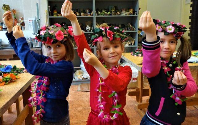 stojące obok siebie trzy dziewczynki wróżowych wiankach izgirlandą kwiatów naszyi. Ręce mają uniesione zjednej strony dogóry. Połączone palce udłoni naśladują pąki kwiatowe.