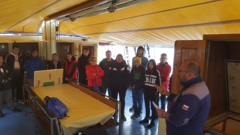 Bosman Piotr przeprowadza szkolenie naśródokręciu dla uczestników rejsu - wtle widać przy stole 13 osób