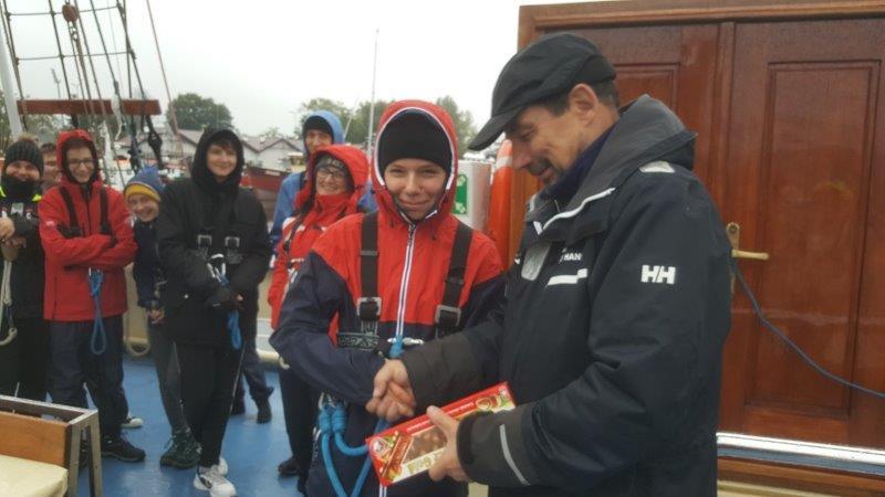 Kapitan wręcza uczestnikowi rejsu tzw. Prezesowi dużą czekoladę zorzechami, wtle 7 uśmiechniętych osób