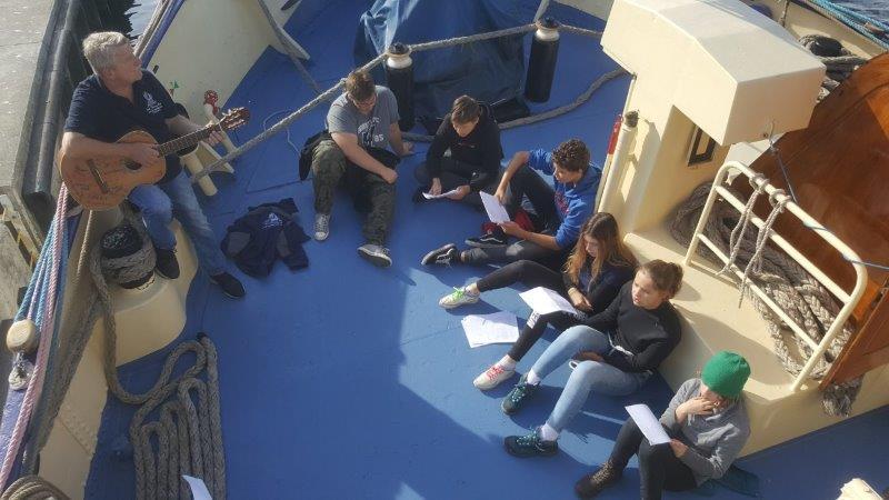 Mechanik Jurek przygrywa nagitarze oparty oburtę anapokładzie wczęści dziobowej siedzi 6 uczestników rejsu, którzytrzymają wrękach teksty szant
