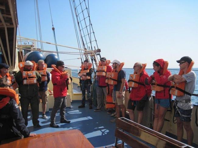 Załoga stała żaglowca orazkadra SKEM wpomarańczowych kapokach podczas szkolenia opuszczenia statku