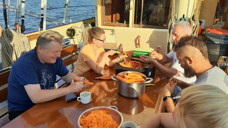 5-osobowa wachta kambuzowa przy stole obiera marchewkę dosurówki