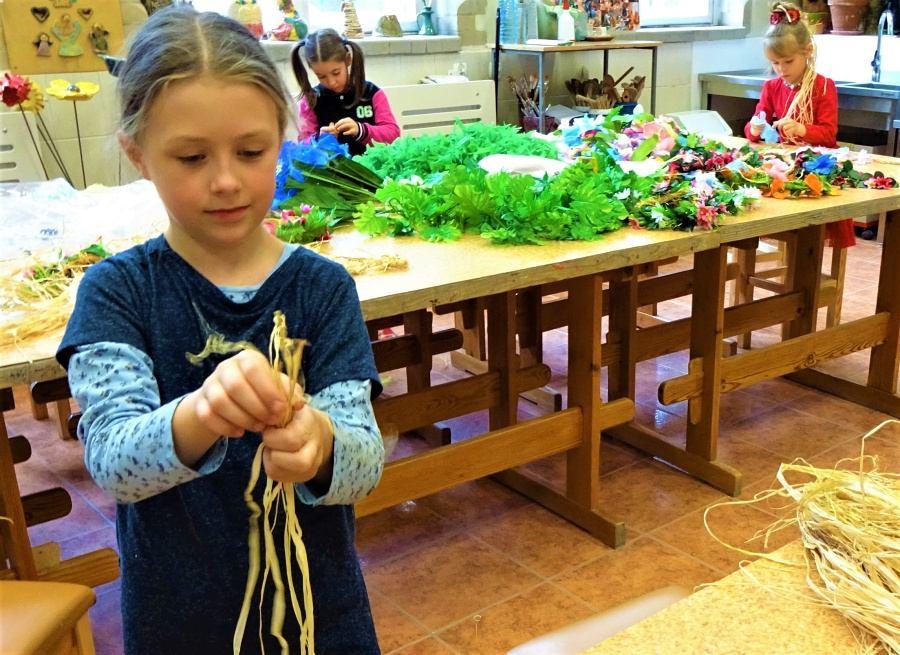 stojąca dziewczynka trzyma w dłoni długie kawałki rafii. W tle dwie dziewczynki wykonują ozdoby z płatków kwiatowych(lei). Na stole rafia, sztuczne kwiaty i liście.