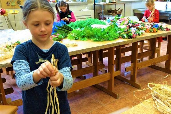 stojąca dziewczynka trzyma wdłoni długie kawałki rafii. Wtle dwie dziewczynki wykonują ozdoby zpłatków kwiatowych(lei). Nastole rafia, sztuczne kwiaty iliście.