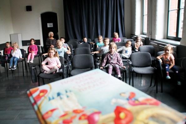 Grupa przedszkolaków siedzi nakrzesłach wsali multimedialnej, napierwszym planie książka
